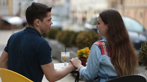 Loving couple sitting at street open-air cafe Footage