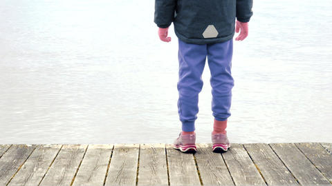 Child standing on wooden jetty and looking at water. Tranquil scene by sea with  Footage