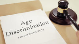 Age Discrimination verdict folder with gavel placed on desk of judge in court Footage