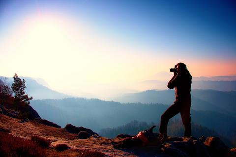 Professional photographer takes photos with mirror camera on peak of rock. Dream Photo