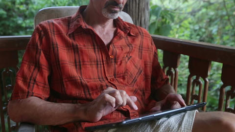 Old Man Prints Text on Tablet PC at Verandah Live Action