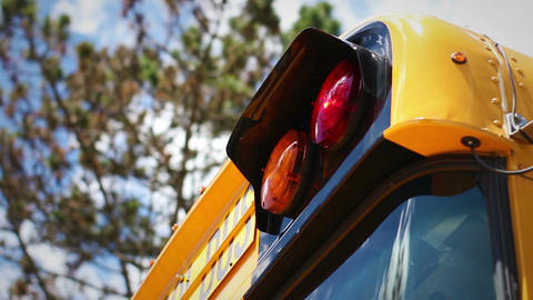 School lights blinking on the upper front of modern school bus with blue sky in  Live Action