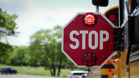 The back of school bus stop sign lights flashing and blinking near playground Footage