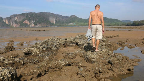 Old Man Walks along Stones at Low Tide Footage