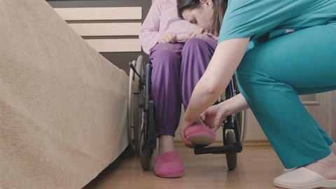 Young nurse caring of elder disabled woman in wheelchair Footage