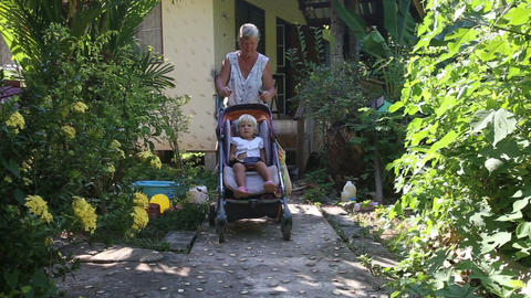 Grandmother Carries Blonde Toddler in Pram Live Action