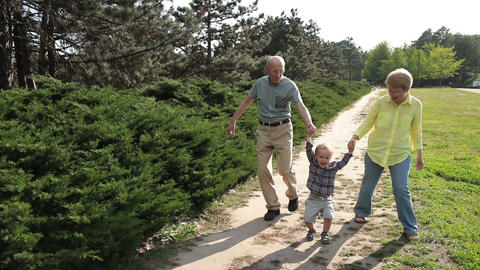Grandparents lifting up toddler boy outdoor Footage