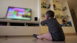 Little baby sit on the house floor and watch blurred content on TV Footage