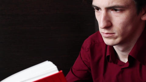 A young guy in a red shirt calmly reads a red book Archivo