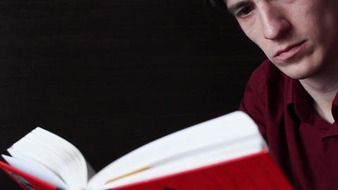 A young guy in a red shirt reading a red book Live Action