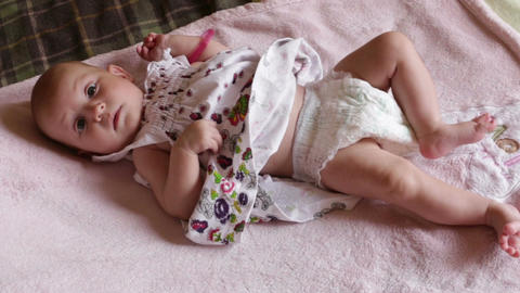 Small Baby Girl in Pretty Dress Lies on Blanket Footage