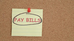 Pay bills reminder note on a bulletin board Footage
