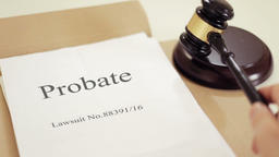 Probate lawsuit documents folder with gavel placed on desk of judge in court Footage