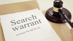 Search warrant document with gavel placed on desk of judge in court Footage