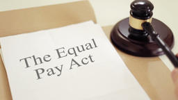 The Equal Pay Act written on folder with gavel placed on desk of judge in court Footage