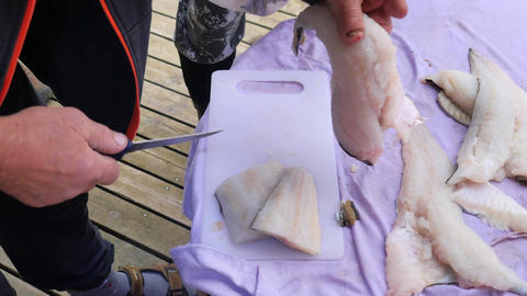 Fish fillet cutting on the street seafood market. Male hands are preparing fish  Footage
