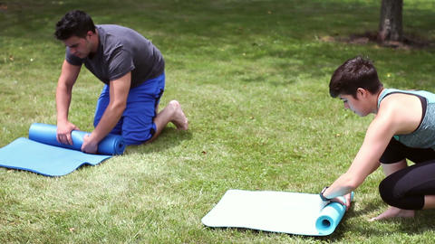 Young cute millennial couple finishing up their yoga session and rolling up mats Footage