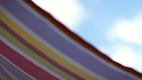 Close up of colorful striped umbrella waving against clear blue sky Footage