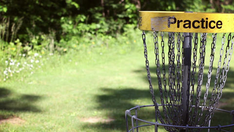 Camera pans to practice Disc golf basket in empty field Footage