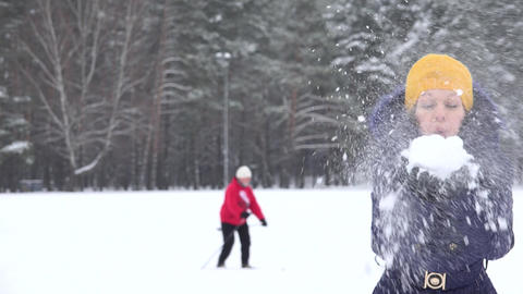 Playful woman with yellow hat blow fluffy snow and skier man on background. 4K Footage