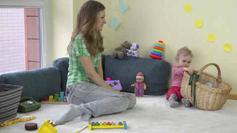 mother woman with adorable toddler daughter girl put toys in basket Live Action