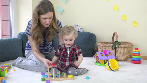 Mom playing with baby colored wooden blocks Footage
