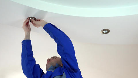 worker man install or replace halogen light lamp into ceiling Footage
