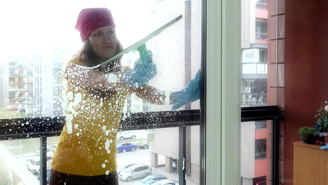 Smiling girl woman spraying chemical and washing window Footage