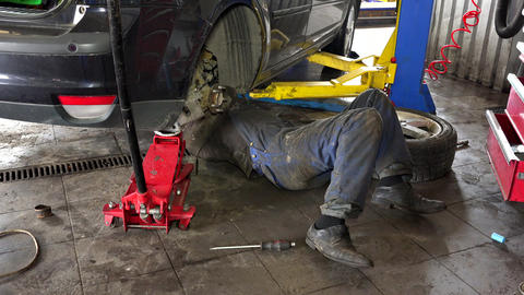 Mechanic lying and working under car at repair garage Footage