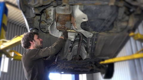 Exhaust of a car on bridge at auto repair shop with a mechanic underneath Footage
