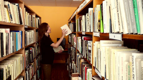 Young female librarian girl putting books in wooden library shelf Footage