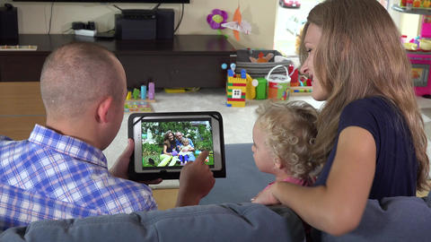 man woman and toddler girl watching family photos on tablet pc at home Footage