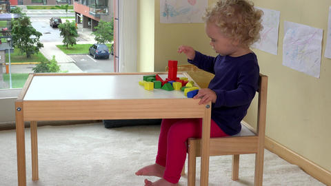 Little toddler girl playing with wooden bricks toys near table at home Footage