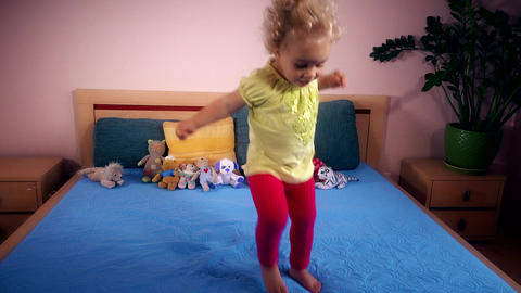 Naughty toddler girl jumping and falling on bedroom Footage