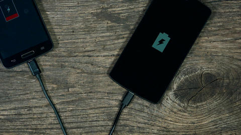 smart phones charging on grunge wood background. Status on screen Footage