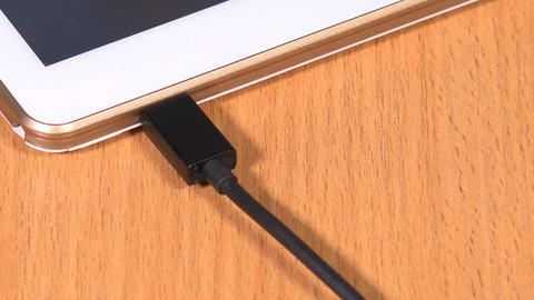Hand unplug black micro usb cable from smart tablet computer Footage