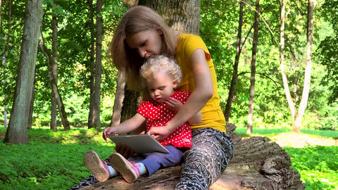 Mother with toddler daughter girl using tablet computer sit on fallen tree trunk Footage