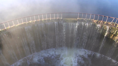 Water flowing through dam with fog rising in morning Footage