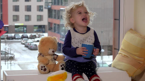 Naughty child girl with tea cup and friend teddy bear sit near window Footage