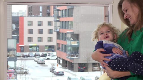Loving mother swing naughty daughter girl on hands near window. Snow fall Footage