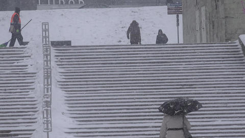 People walking in heavy snowstorm and city worker clean snow with broom Footage
