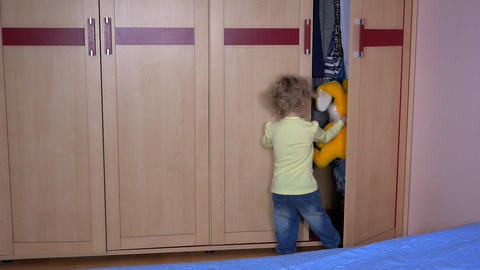 Playful boy with bunny friend hiding in wardrobe Footage