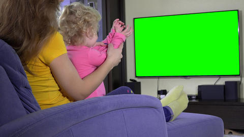 Young mother with her daughter girl relax on sofa and watch tv. Green screen Live Action