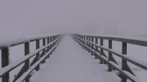foggy snowy landscape with mother and a child on wooden old bridge Footage