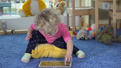 Cute toddler girl use tablet pc sitting on blue carpet. Happy child clap hands Footage