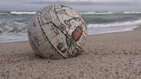 Retro globe on the sand by the wavy sea Footage