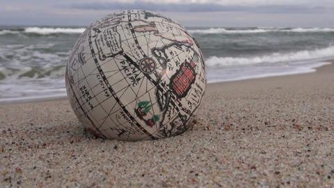 Retro globe on the sand by the wavy sea ビデオ