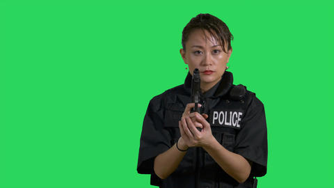 Asian Chinese policewoman looks around and holds pistol on green screen Live影片
