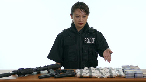 Asian female police officer pointing to seized goods 1 Live影片