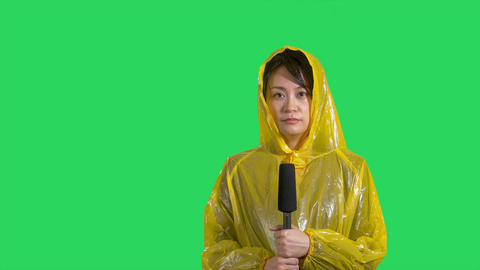 Chinese news reporter reporting bad storm on green screen Footage